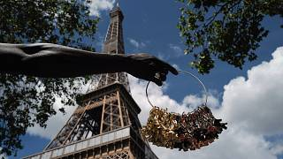 A street vendor displays miniatures of the Eiffel Tower outside of the closed monument in Paris. The iconic structure has been closed for more than three months since March.