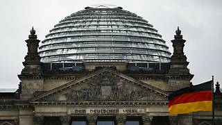 A German national flag waves in front of the German parliament building Reichtstag in Berlin, Germany