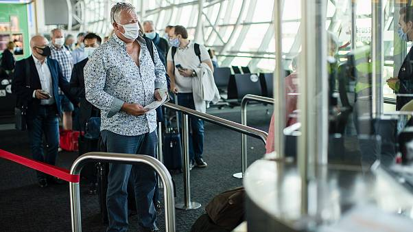 Passengers, wearing face masks to protect against the spread of coronavirus, queue up to board their plane at the Zaventem international airport. Brussels, Belgium