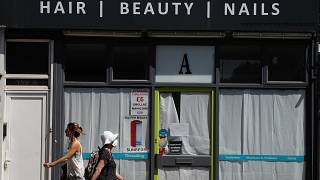 People walk past a closed hair and beauty salon in London, Tuesday, June 23, 2020.
