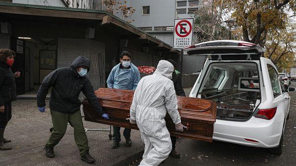 Empleados cargan el ataúd de un fallecido por Covid-19