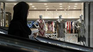 A woman rides an escalator as she looks at a women's dress shop display in a shopping center at Tehran's Grand Bazaar, Iran
