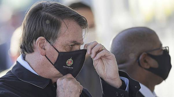 Brazil's President Jair Bolsonaro adjusts his face mask as he speaks to supporters while departing his official residence, Alvorada palace, in Brasilia, Brazil, Thursday, May