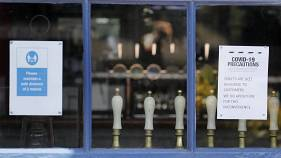 Draft tabs are seen through a window of a closed pub in London, Tuesday, June 23, 2020. Pubs are to reopen in a major easing of lockdown restrictions in England from July 4.