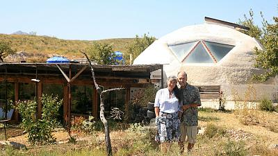 Laura Davies and Dave Buchanan standing outside their eco home.