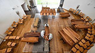 Des employés déchargent d'un camion militaire des cercueils arrivés de Bergame près de Milan pour être inhumés au cimetière Cinisello Balsamo le 27 mars