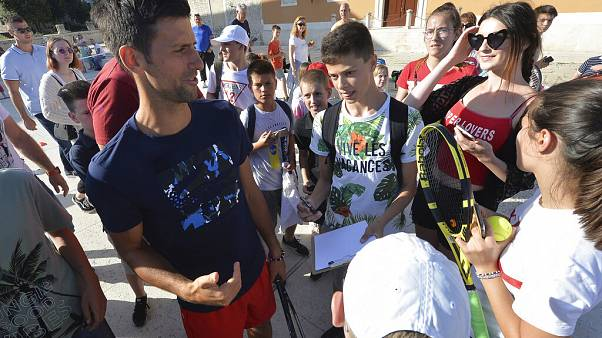 Novak Djokovic, left, talks to children in Zadar, Croatia. Djokovic has tested positive for the coronavirus after organising a tennis tournament in Serbia and Croatia.