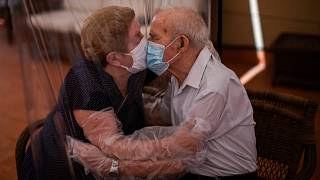 Agustina Cañamero, 81, and Pascual Pérez, 84, hug and kiss through a plastic film screen to avoid contracting the new coronavirus at a nursing home in Barcelona, Spain