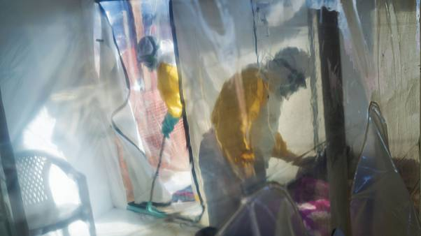 FILE - In this July 13, 2019 file photo, health workers wearing protective suits tend to an Ebola victim kept in an isolation cube in Beni, Congo.