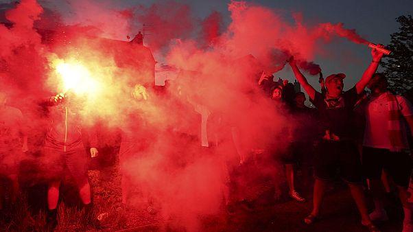 Un gruppo di tifosi del Liverpool festeggia la vittoria della Premier League davanti ad Anfield Road