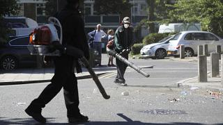 Volunteers clean up the streets following overnight violent confrontations in Brixton, London.
