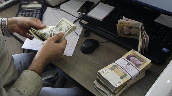 A currency exchange bureau worker counts US dollars, in downtown Tehran, Iran