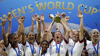 United States' Megan Rapinoe lifts up a trophy after winning the Women's World Cup final soccer match between US and The Netherlands at the Stade de Lyon, France