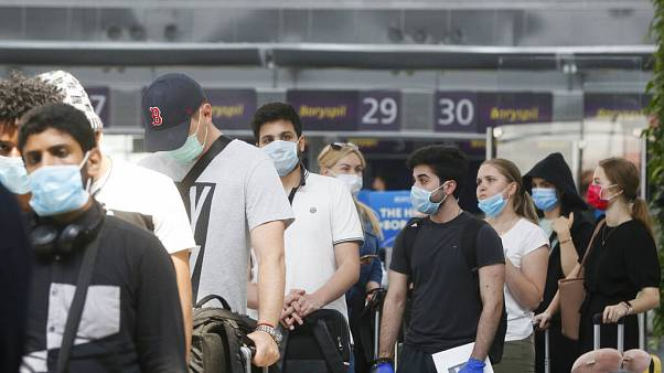 Passengers wearing face masks to protect against coronavirus pass check-in procedure at Boryspil International Airport outside Ukraine's capital Kyiv