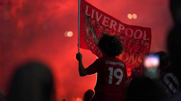 Liverpool supporters celebrates outside Anfield Stadium in Liverpool, England, Thursday, June 25, 2020
