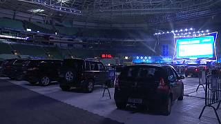 سيارات مصطفة يجلس فيها أصحابها لمشاهدة فيلم على شاشة عملاقة وسط ملعب لكرة القدم في ساو باولو البرازيلية - 2020/06/25