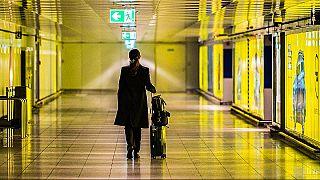 Una donna cammina con la sua valigia lungo un corridoio vuoto dell'aeroporto del Reno-Meno. 12 marzo 2020