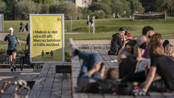 People enjoy the warm evening weather in Malmo, Sweden, Tuesday May 26, 2020 as a sign reads 'In Malmo everything is near. But now we need to keep a distance'.