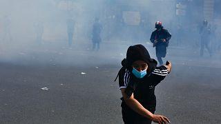 A protestor flees tear gas
