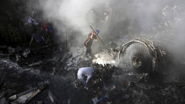 In this May 22, 2020 file photo, volunteers look for survivors of a Pakistan International Airlines plane that crashed in a residential area of Karachi, Pakistan.