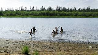 children play in the Krugloe lake outside Verkhoyansk, the Sakha Republic, about 4660 kilometers (2900 miles) northeast of Moscow, Russia.