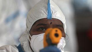"""ممرض يقيس درجة حرارة امرأة في مخيم في """"درافي"""" في مومباي في الهند - 2020/06/26"""