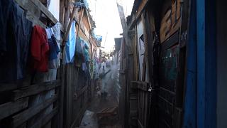 Volunteers spreading disinfectant in alleyways of squat