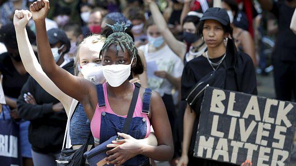 Deux jeunes femmes participent à un rassemblement contre le racisme à Berlin