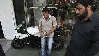 A street money exchanger, center, counts US dollars, in downtown Tehran, Iran