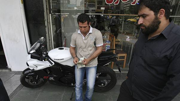 A street money exchanger, center, counts US dollars, in downtown Tehran, Iran