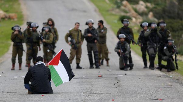 Filistin bayrağı ile ABD Başkanı Donald Trump'ın 'Ortadoğu Barış Planı'na karşı çıkan bir Filistinli eylemci ve İsrail askerleri / Ürdün Vadisi