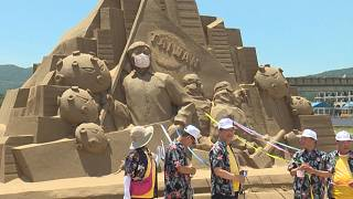 Government ministers getting ready to take down face mask on sand sculpture of health minister