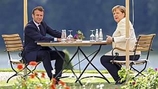 German Chancellor Angela Merkel and French President Emmanuel Macron, left, talk during a bilateral meeting at the German government's guest house Meseberg Castle near Berlin
