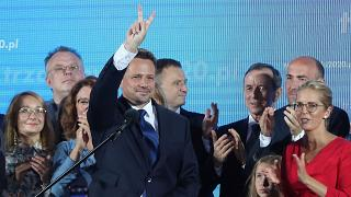 Warsaw Mayor Rafal Trzaskowski, front, reacts to exit poll after voting closed