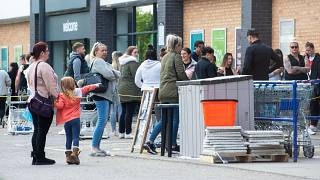 People queue outside a shop in Leicester amid coronavirus social-distancing measures