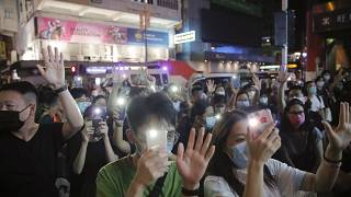 """Protesters gesture with five fingers, signifying the """"Five demands - not one less"""" during a protest in Mong Kok, Hong Kong, Friday, June 12, 2020."""