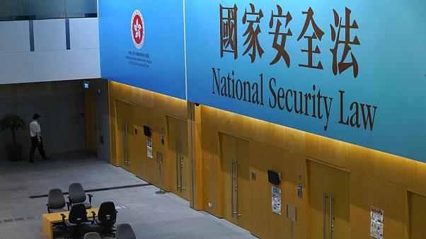 A government staff walks past a big banner featuring the Hong Kong National Security Law at the government headquarters in Hong Kong, Tuesday, June 30, 2020.