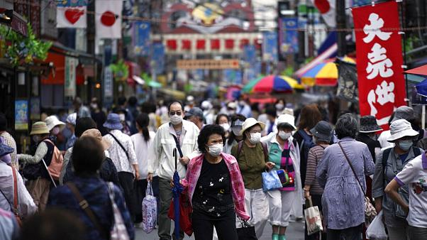 A street is crowded by shoppers in Tokyo