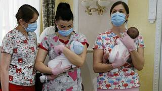Nurses hold babies born from Ukrainian surrogate mothers prior to them meeting their parents, in Kyiv, Ukraine, Wednesday, June 10, 2020.