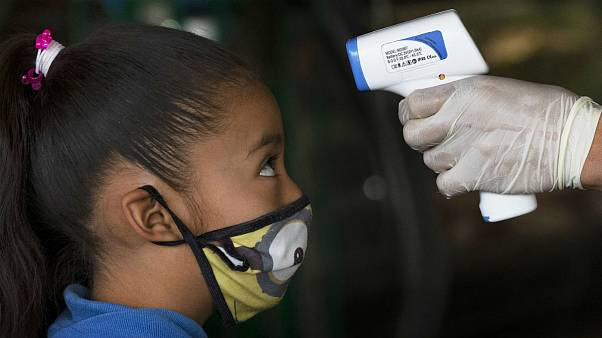 A health worker takes a child's temperature to help curb the spread of the new coronavirus, at the Central de Abasto market in Mexico City