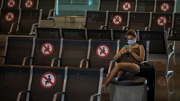 A passenger sits at Barcelona airport in Barcelona, Spain