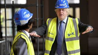 Britain's Prime Minister Boris Johnson talks with year 10 pupil Vedant Jitesh during a visit to the construction site of Ealing Fields High School in London, June 29, 2020.