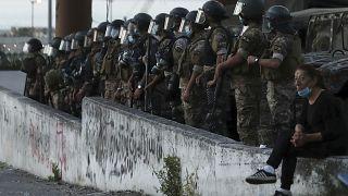 متظاهرة مناهضة للحكومة تجلس بالقرب من جنود الجيش اللبناني في بيروت، لبنان.