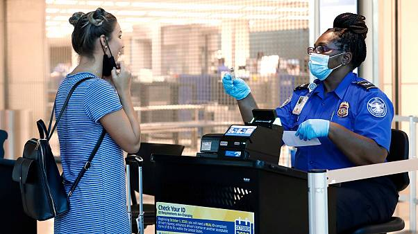 L'agent de la TSA Patrisa Johnson, à droite, aide un voyageur à passer la sécurité avant de s'envoler de Love Field à Dallas, le mercredi 24 juin 2020.