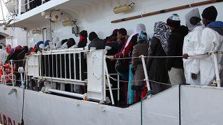 مهاجرون ينتظرون النزول من الساحل الإيطالي