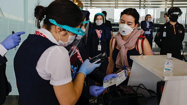Sabiha Gökçen Havalimanı'ndan Londra'ya gitmek üzere olan uçağın yolcularına maskeli bir görevli bilet kontrolü yapıyor