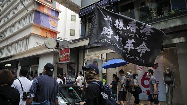 Demonstrant mit Flagge, auf der zur Befreiung Hongkongs aufgerufen wird