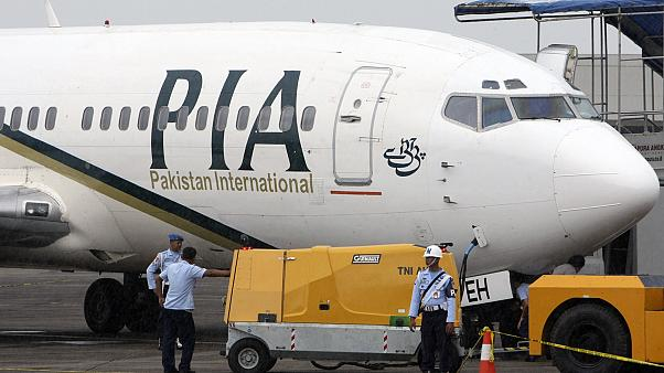 A Pakistan International Airlines passenger jet is parked on the tarmac at a military base in Makassar, Indonesia.