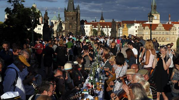 Residents sit to dine on a 500 meter long table set on the medieval Charles Bridge  in Prague, Czech Republic, Tuesday, June 30, 2020.