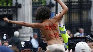 A FEMEN activist shouts slogans against female genital mutilation (FGM) during a protest opposite the Houses of Parliament in London.